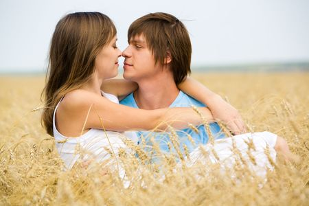 passionate kissing: Image of handsome man holding girl and looking at her
