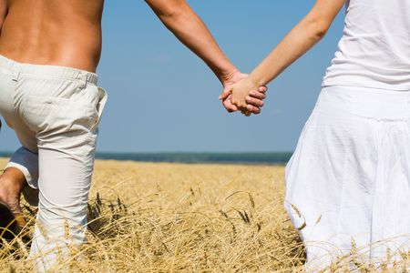 Close-up of woman and man holding by hands in the field  photo