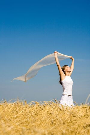 Portrait of pretty teenager holding fabric and standing in wheat field  photo