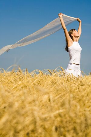 Image of golden wheat on the background of enjoying woman  photo