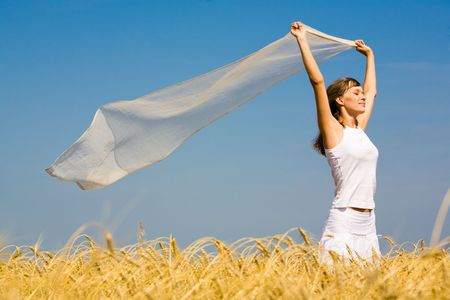 blowing wind: Portrait of pretty woman wearing white clothes and holding fluttering chiffon scarf in her hands