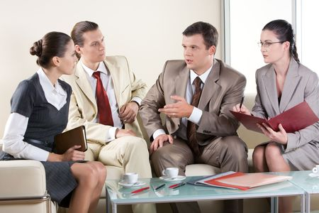 Portrait of serious business people sitting next to each other and communicating at business meeting Stock Photo - 3708993