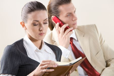 Portrait of pretty employee looking into notebook on background of man talking on the phone Stock Photo - 3708992
