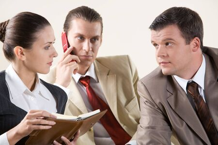 Photo of two colleagues looking at each other during meeting on background of phoning man Stock Photo - 3708996