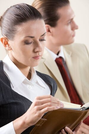 Image of pensive business lady watching into notebook in her hands with man at background Stock Photo - 3708997