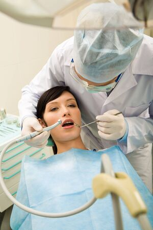 Photo of pretty girl with the dentist over her holding drilling instrument and mirror Stock Photo - 3708149