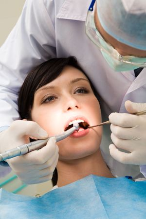 Close-up of young female with open mouth at the dentist office while doctor examining her oral cavity Stock Photo - 3708172