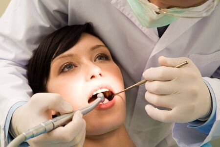 Image of young woman keeping her mouth open while dentist examining it Stock Photo - 3708116