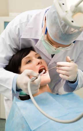 dolor de muelas: Vertical imagen de la mujer paciente con su dentista sobre control hasta los dientes y la perforaci�n ellos