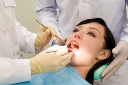 Photo of female patient with open mouth while her teeth being examined supported by assistant Stock Photo - 3708144