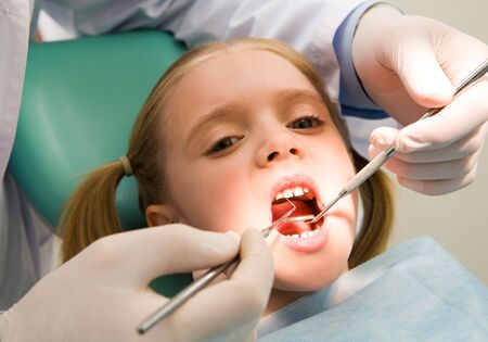 examined: Photo of small girl looking at camera with open mouth while it being examined by dentist