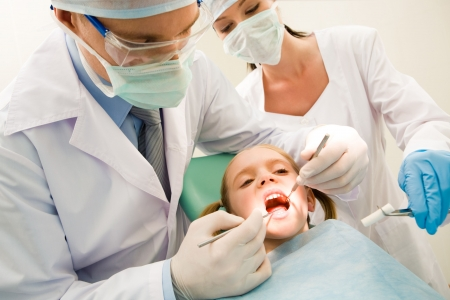 Image of dental checkup being given to little girl by dentist with assistant near by photo