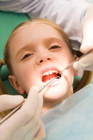 Close-up of little girl opening her mouth for dental checkup in stomatological office photo
