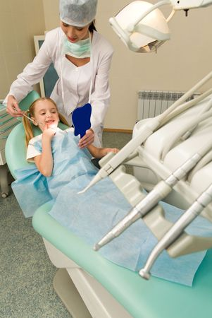 Dental inspection and treatment instruments with dentist and her patient at background photo