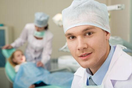 Portrait of confident doctor on background of his assistant with patient Stock Photo - 3709038