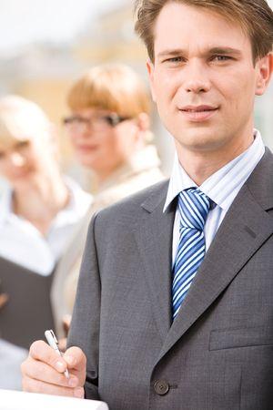 female boss: Portrait of male professional on background of businesswomen