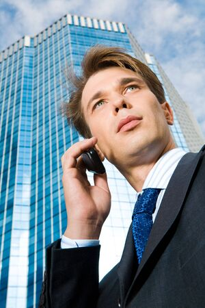 View from below of confident businessman speaking on the phone outdoors photo