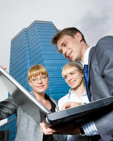 View from below of business team looking at laptop monitor outdoors