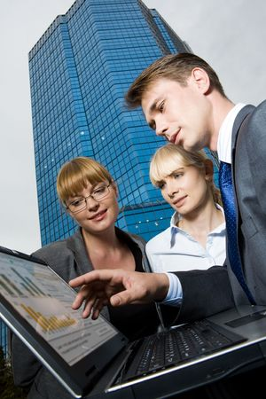 Image of friendly business group looking at laptop screen while man pointing at it photo