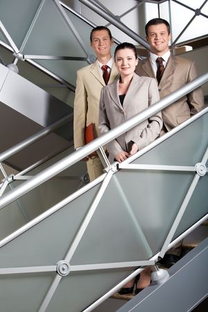 Portrait of smiling business partners standing behind railing and looking at camera photo
