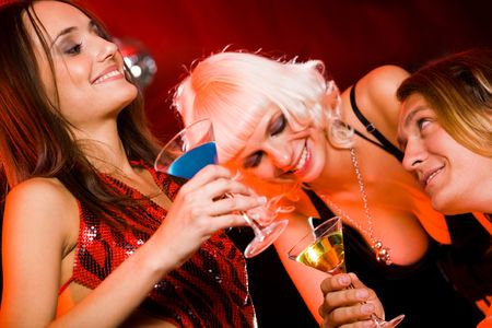 stylish couple: Two happy girls chatting and drinking spirits with smiling guy during party