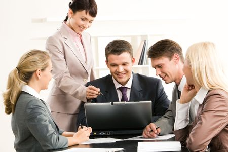 Portrait of friendly group sitting at table while three managers looking at laptop screen and businesswoman pointing at it photo