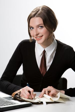 Portrait of cheerful student sitting at workplace and making notes while looking at camera with smile photo