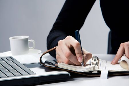 Human hand writing something in notebook with laptop near by Stock Photo - 3707926