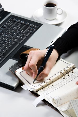 Above view of female hand writing in notepad with laptop and cup near by Stock Photo - 3707928