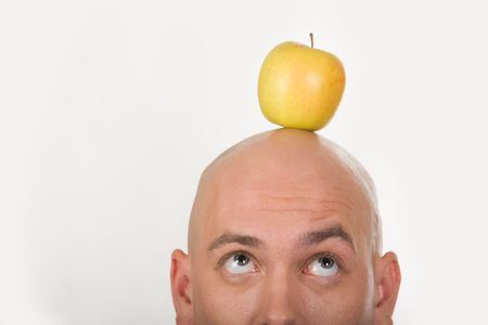Close-up of bald male head with yellow apple on it  photo