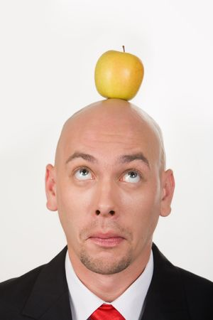 Funny businessman having apple on his head and looking at it photo