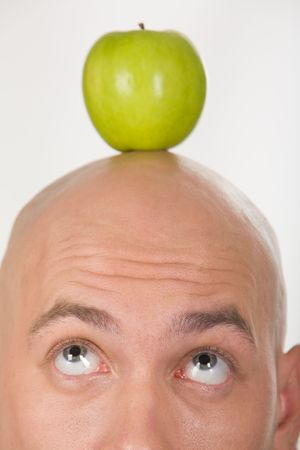 Close-up of bald head with green apple on its top photo