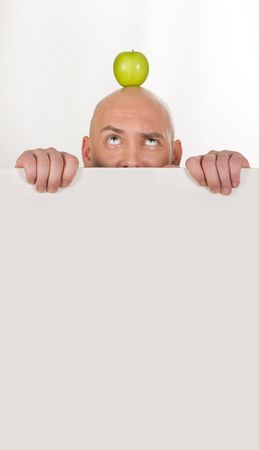 Image of annoyed man looking at apple on his bald head photo