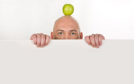 Upper part of bald man�s face with apple on top behind white partition Stock Photo - 3709054