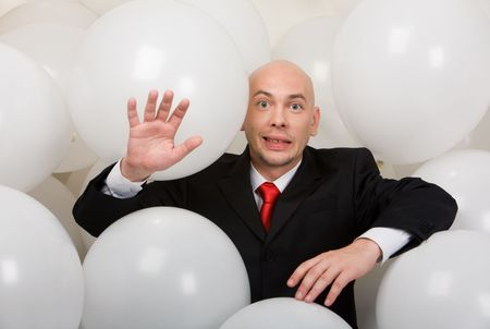surrounded: Image of funny man in suit surrounded by balloons looking at camera