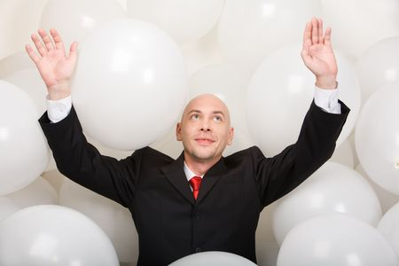 Photo of joyful man wearing suit inside balloons raising his arms Stock Photo - 3709030