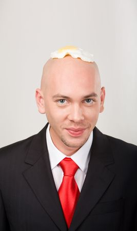 Portrait of smiling male with omelet on top of bald head photo