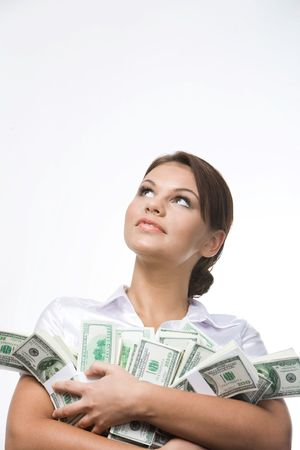 Portrait of charming lady holding bills of dollars and looking upwards photo
