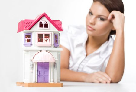 Miniature toy house with dreaming woman looking at it near by photo