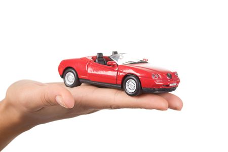 Close-up of red toy car on female�s palm over white background photo