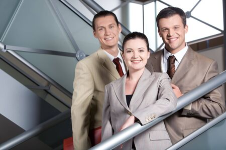 Portrait of happy businesswoman standing on staircase with two men behind photo