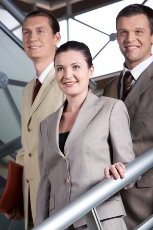 Portrait of smiling business people standing on stairs and looking aside photo