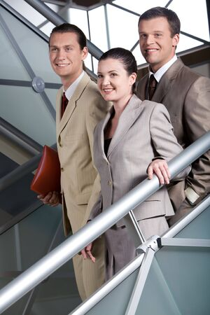 Business group going downstairs with smiles and looking aside photo