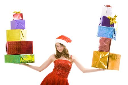 Photo of happy girl wearing red dress and Christmas cap holding stack of presents on each palm photo