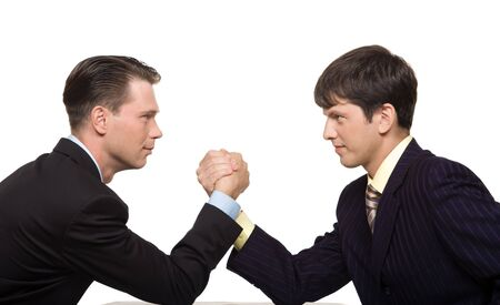 contrary: Two businessmen looking at each other seriously while doing arm wrestling