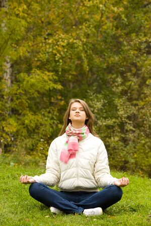 Portrait of calm girl meditating outside in autumn photo