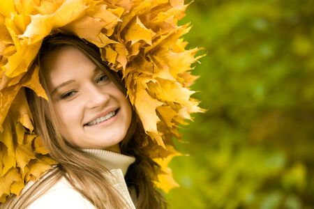 Smiling girl with maple wreath looking at camera on green background photo