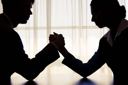 Silhouette of business competitors doing arm wrestling in office photo
