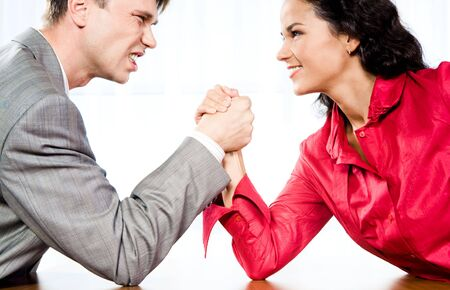 Portrait of smiling woman and angry man fighting by their arms