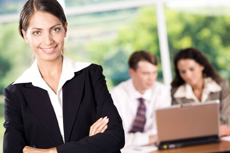 Portrait of happy woman wearing suit looking at camera with smile in working environment photo